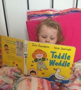 A toddler lays in bed and reads Toddle Waddle, a picture book by Julia Donaldson and Nick Sharratt