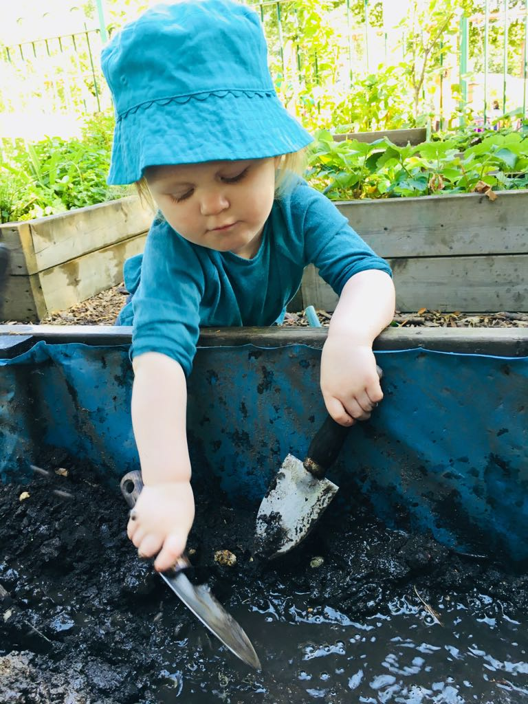 A toddler in a blue hat and t-shirt with a trowel in each hand stretches to reach some wet mud in a trough in messy play session at a mud club.
