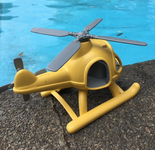 A yellow Green Toys helicopter sits on the edge of a public paddling pool