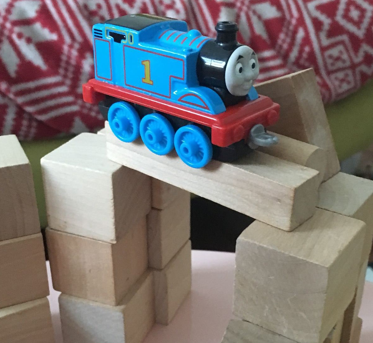 A toy Thomas the Tank Engine train sits atop a bridge constructed of traditional wooden bricks