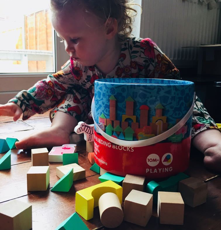 A toddler sits on the floor of a room playing with a bucket of traditional wooden blocks