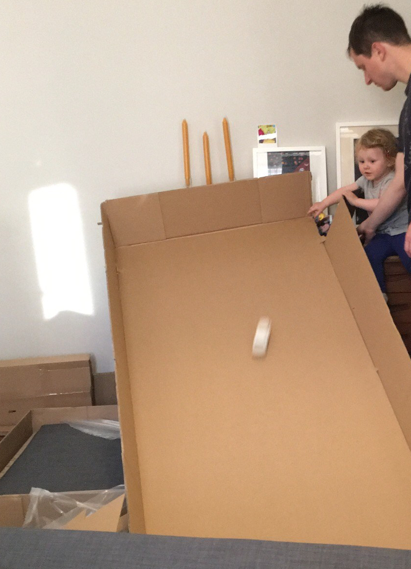 A young child and her father enjoy rolling a toy car down a large piece of cardboard