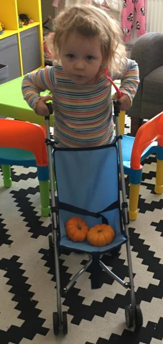 A young child pushing a toy pushchair holding two small pumpkins