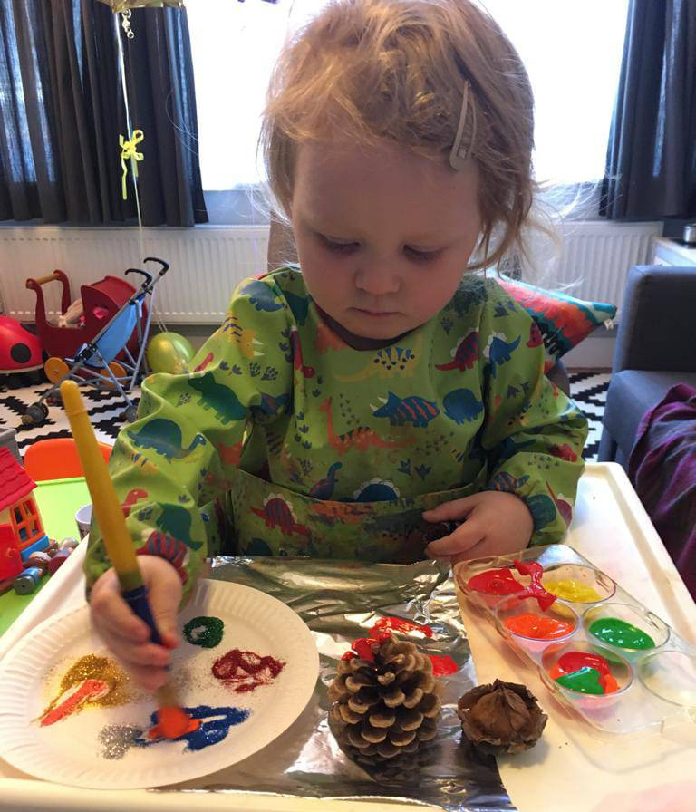 A child in an overall using bright paints and glitter to decorate a paper plate during an activity