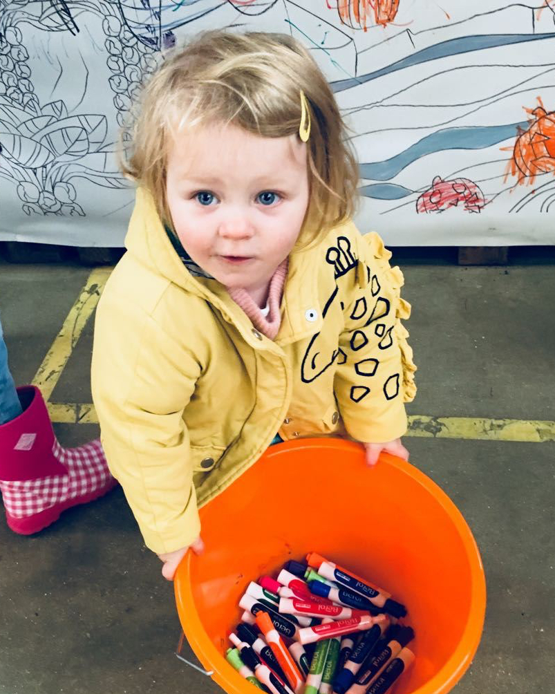 A young child in a yellow coat holding an orange bucket filled with felt tip pens