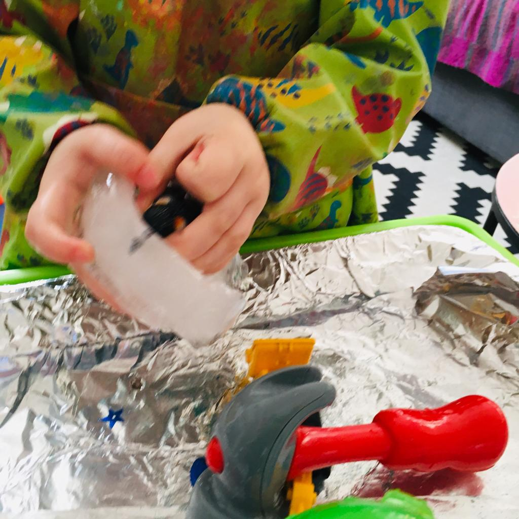 A child trying to remove a toy penguin from a partially thawed block of ice, during a messy play activity.