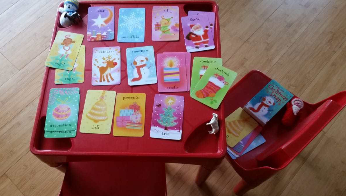 A red table showing a game of snap in progress using Usborne Christmas Snap cards
