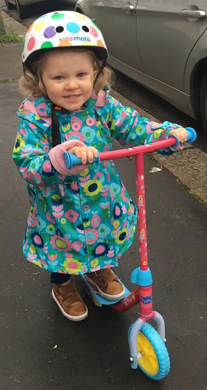 A child smiling and wearing a safety helmet while using on a pink Peppa Pig scooter