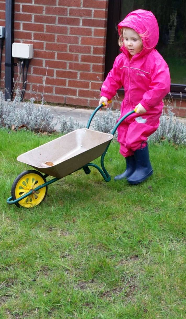 A child in pink overalls and blue wellington boots prepares to push a small wheelbarrow down a hill on a wet day