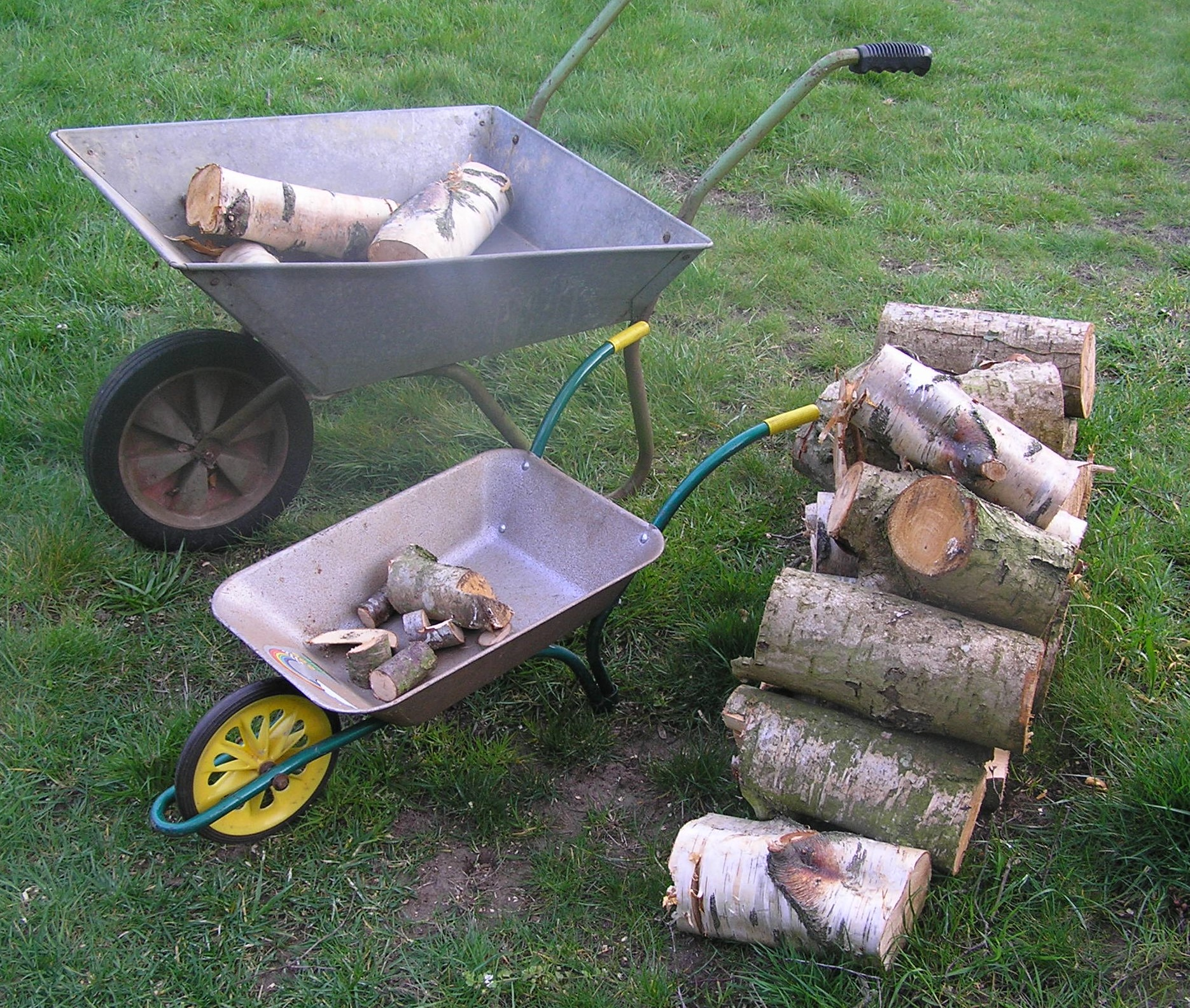 In a garden, an adult wheelbarrow is pictured next to a smaller child's wheelbarrow for comparison, both are filled with logs and there is a stack of cut logs nearby
