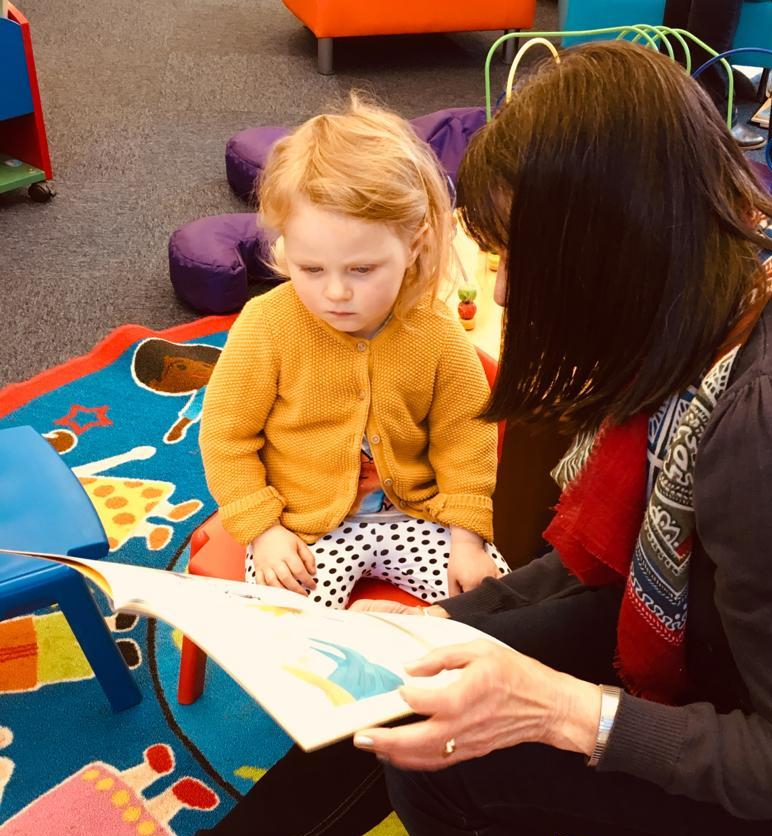 A young child is engrossed in reading a library book with an adult.