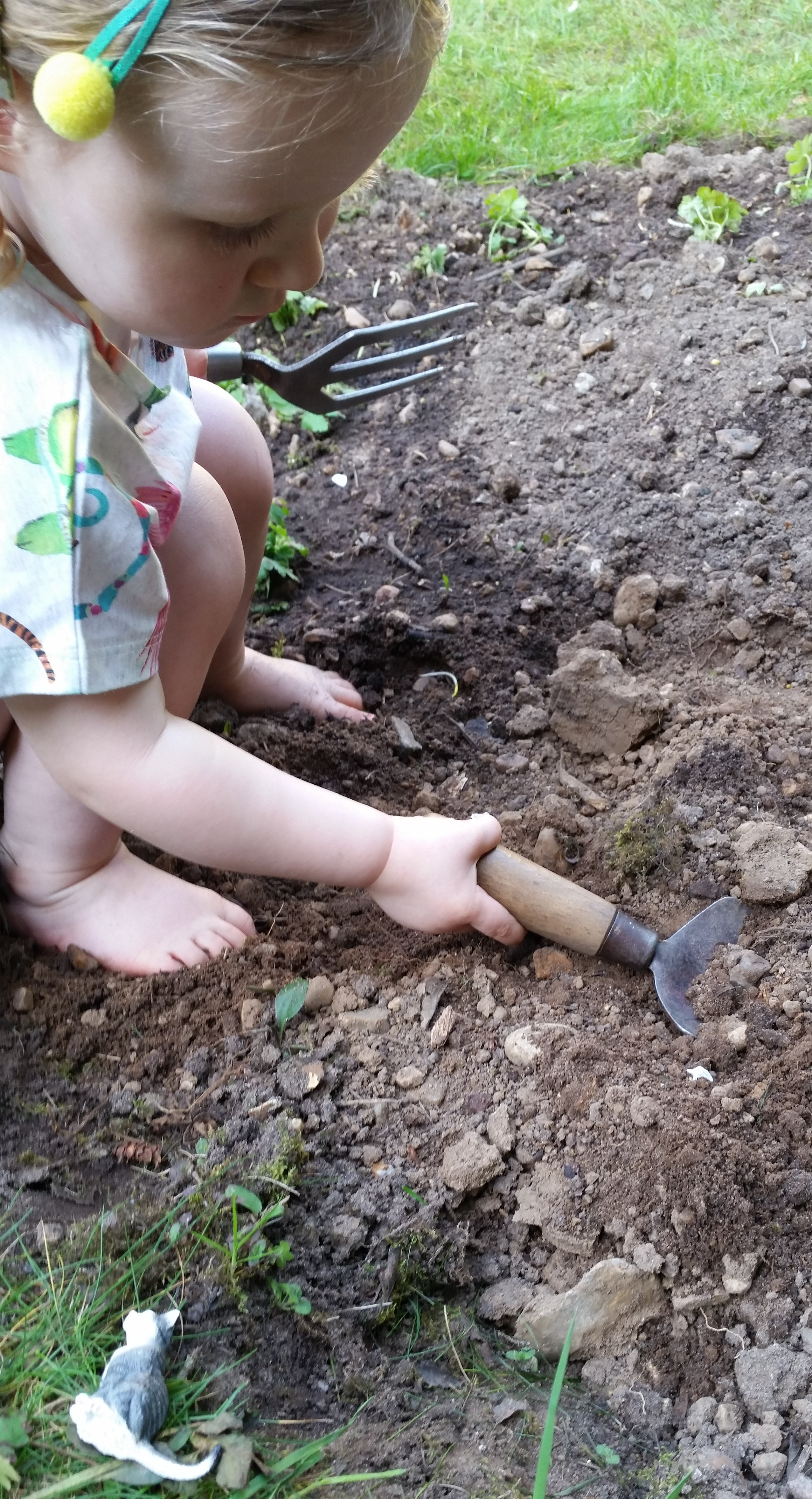 A young child crouches in a flower bed using a trowel during a gardening activity