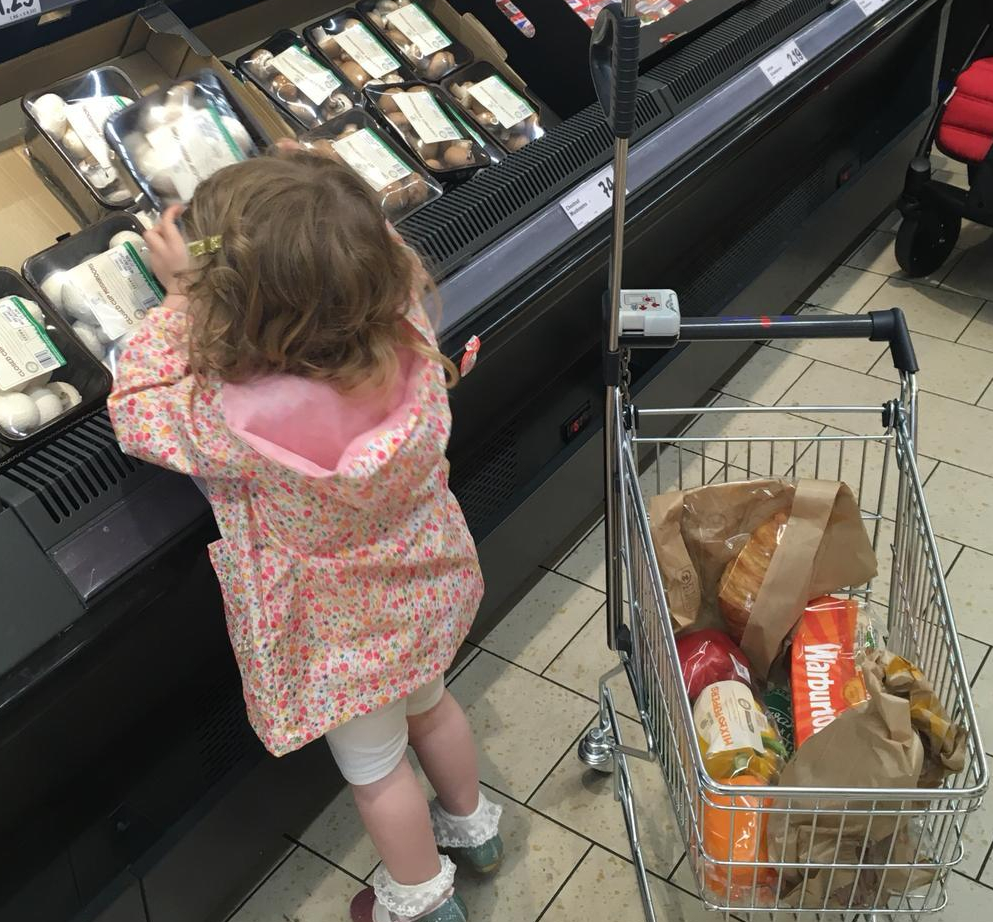 A young child helps her parents select a packet of mushrooms during a shopping trip