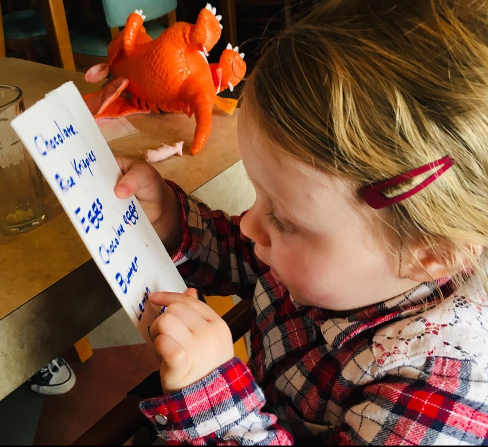 A young child runs her finger down a shopping list as part of a numeracy and literacy activity.