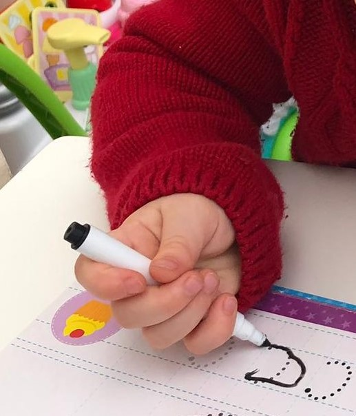 A child using a rudimentary sideways fist-like grip to hold a pen in her hand during a writing activity