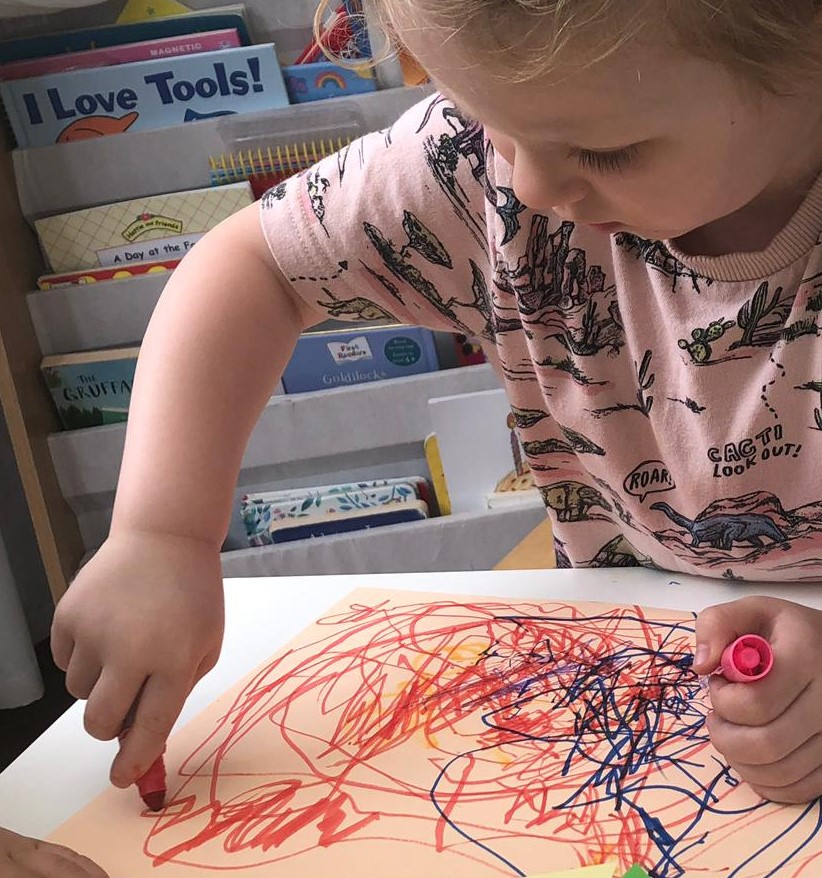 A child practising gripping and controlling a chunky pen during a drawing exercise