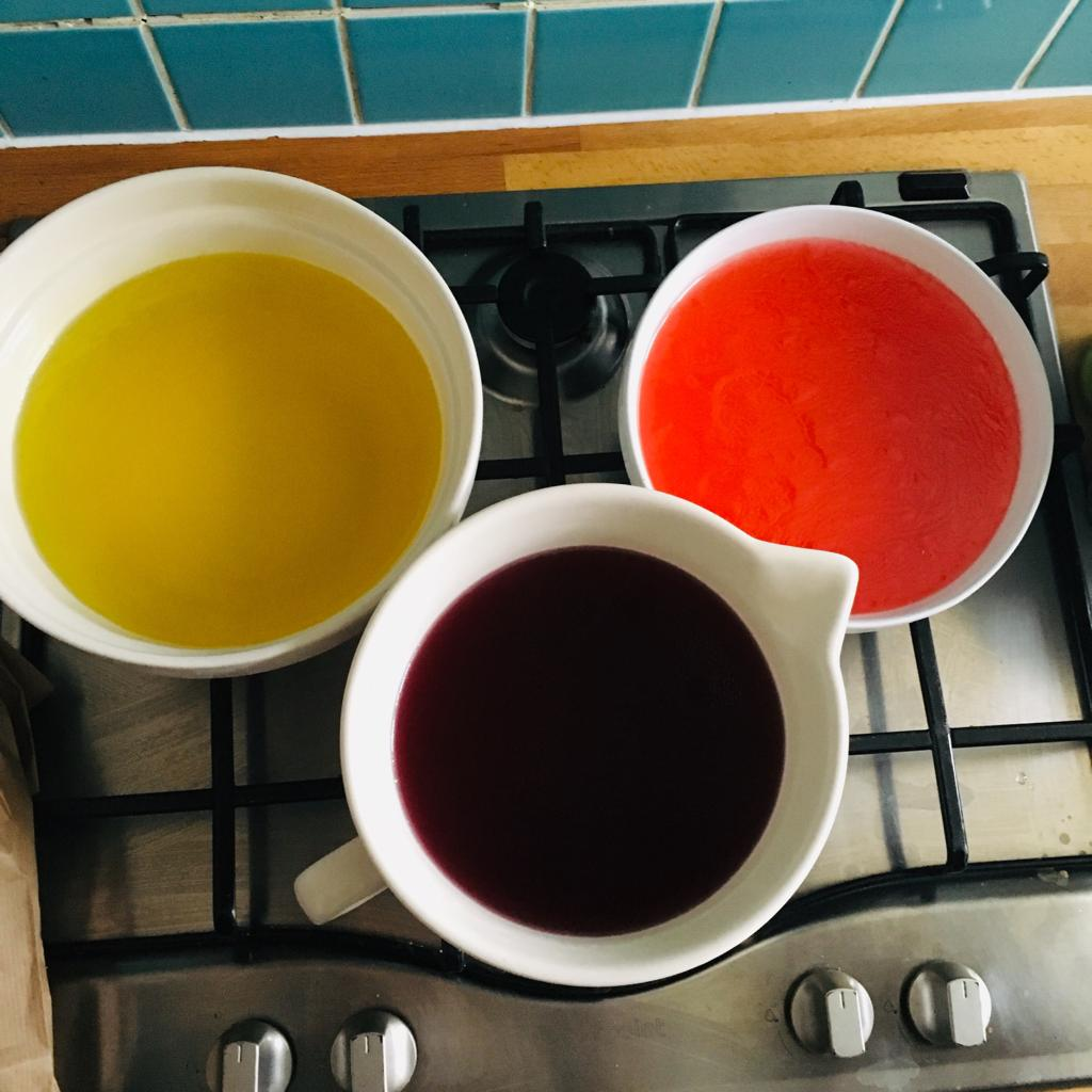 Three large bowls, red, purple and amber, of jelly sitting on a stove top, ready for a messy play activity.