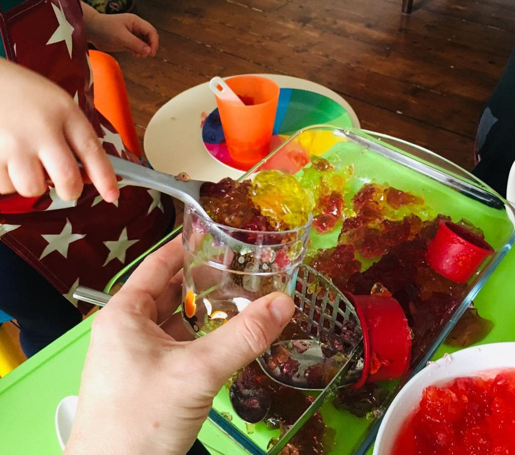 A messy play activity in progress, a child is using an ice cream scoop to serve some jelly (or jello) to an adult who is holding a cup. A potato masher and other cup and cookie cutters are visible.