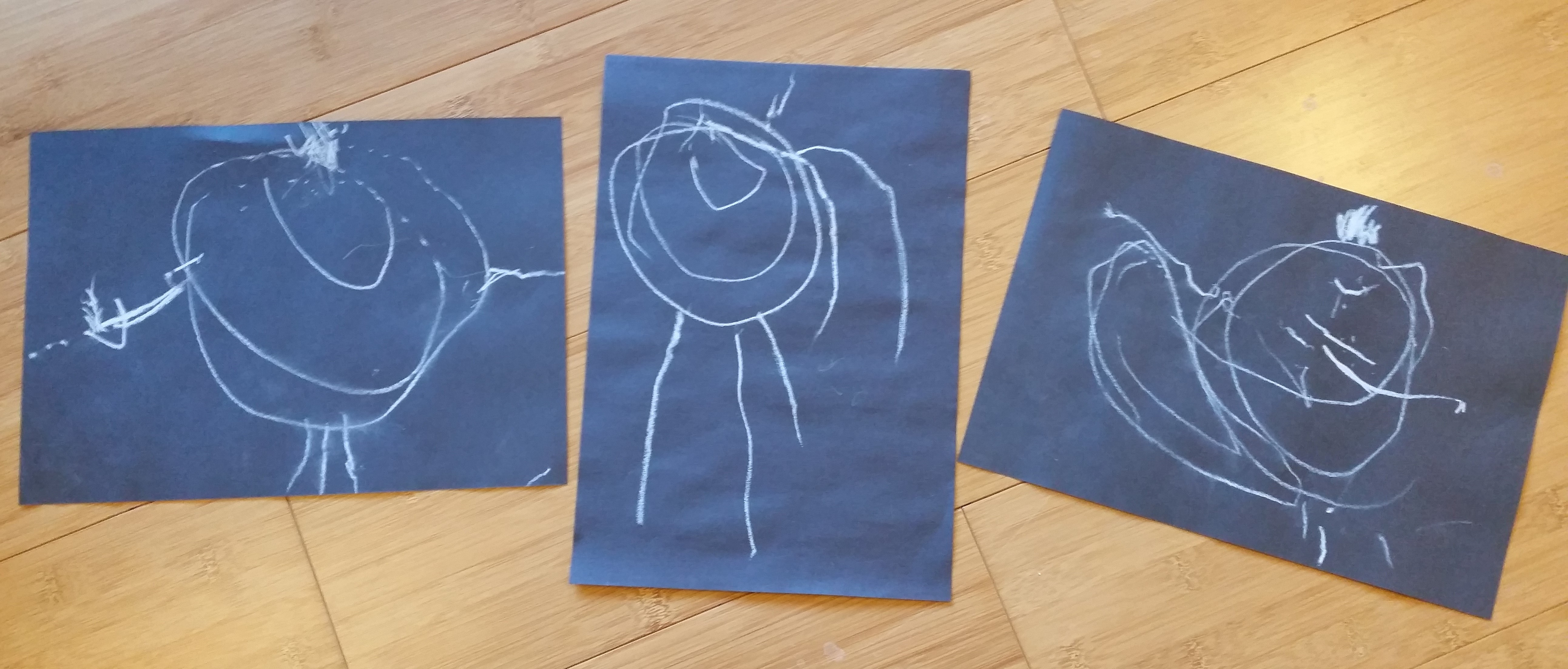 A set of three child's drawings made in chalk on black sugar paper.