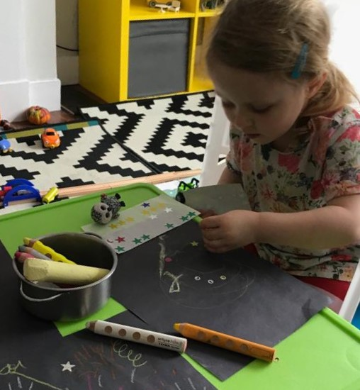 A child using chalks, large pencil crayons and star stickers on a page of black sugar paper as part of an activity
