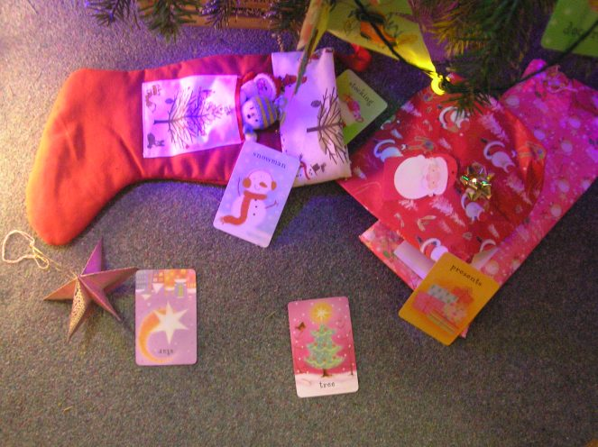 A series of child's Christmas themed flash cards are shown next to Christmas stocking and some gifts beneath a Christmas tree