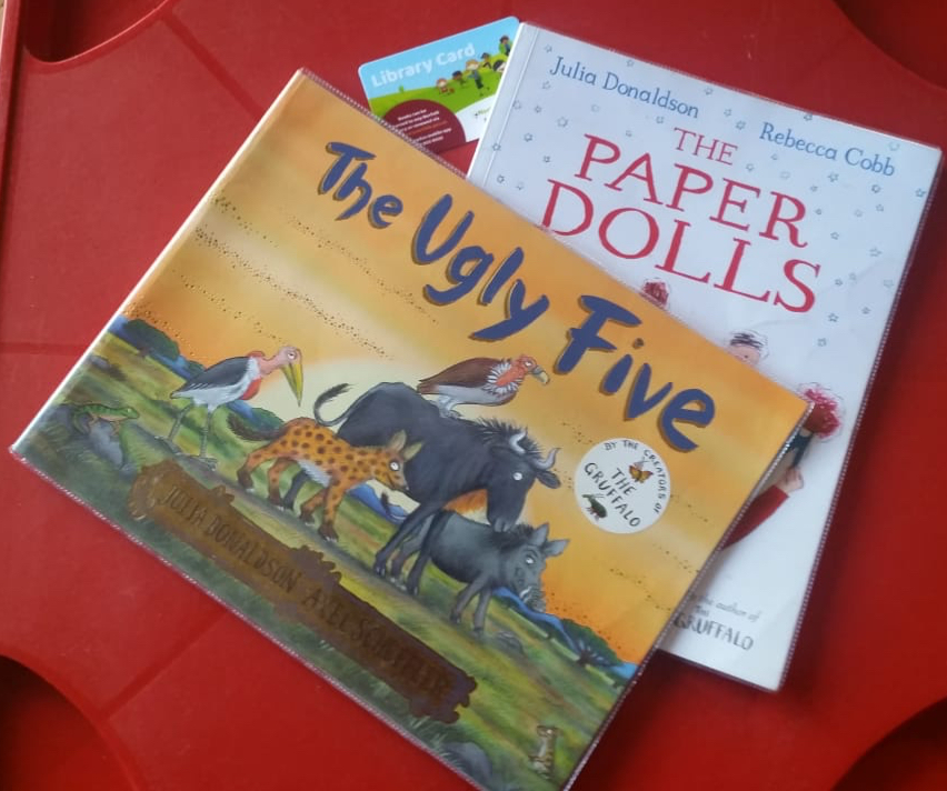Copies of two library books: The Ugly Five by Julia Donaldson and Axel Scheffler and The Paper Dolls by Jilia Donaldson and Rebecca Cobb