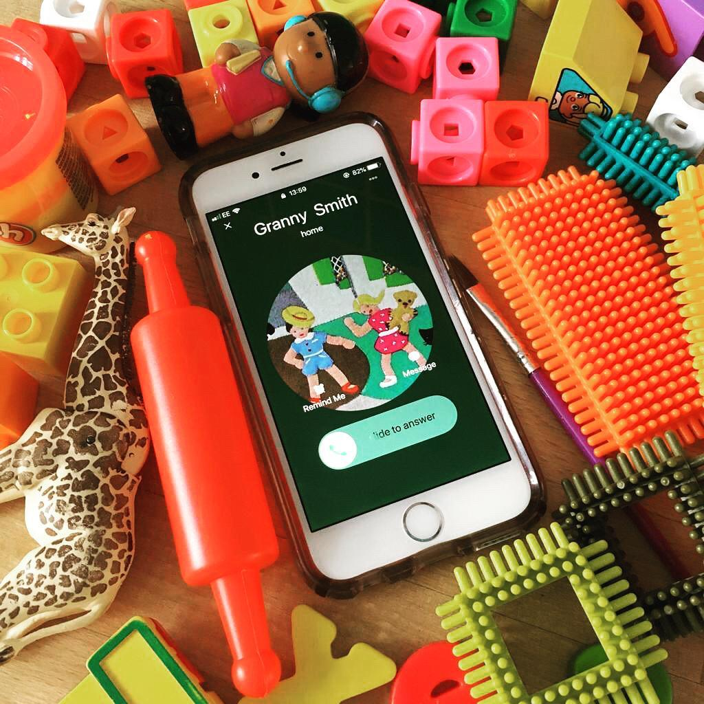 An Apple iPhone amid a pile of toys, showing an incoming call from Granny Smith