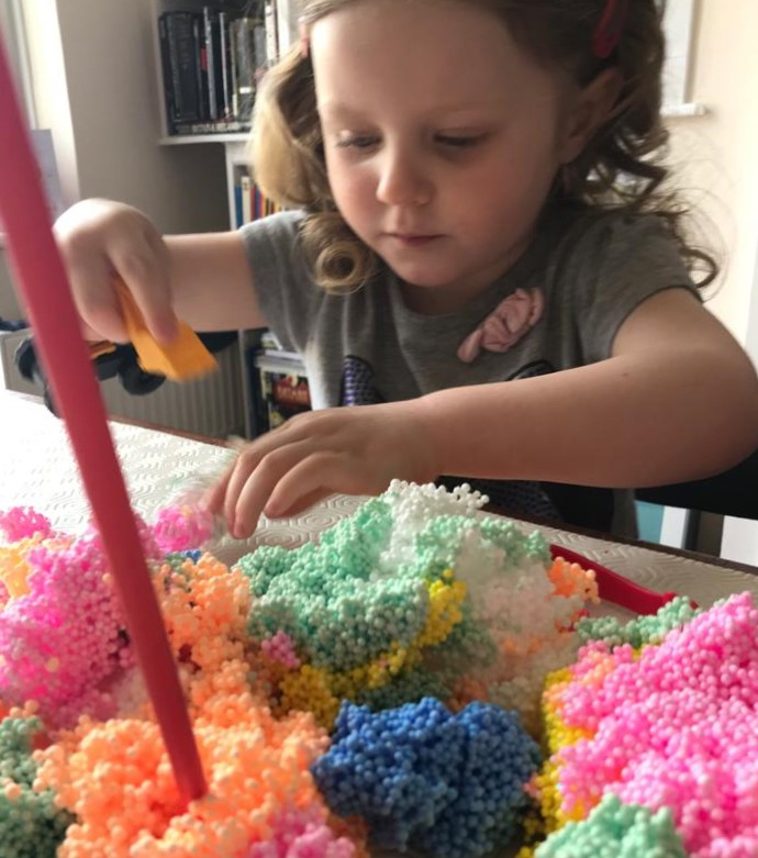 A young girl using multicoloured play foam and straws for a session of messy play.