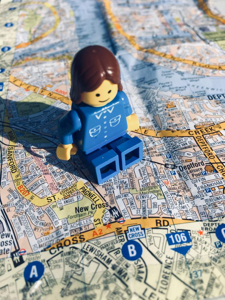 A female Lego minifigure sitting on a map of London