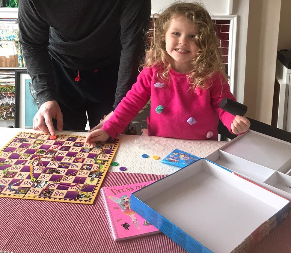 A young child playing a board game of snakes and ladders