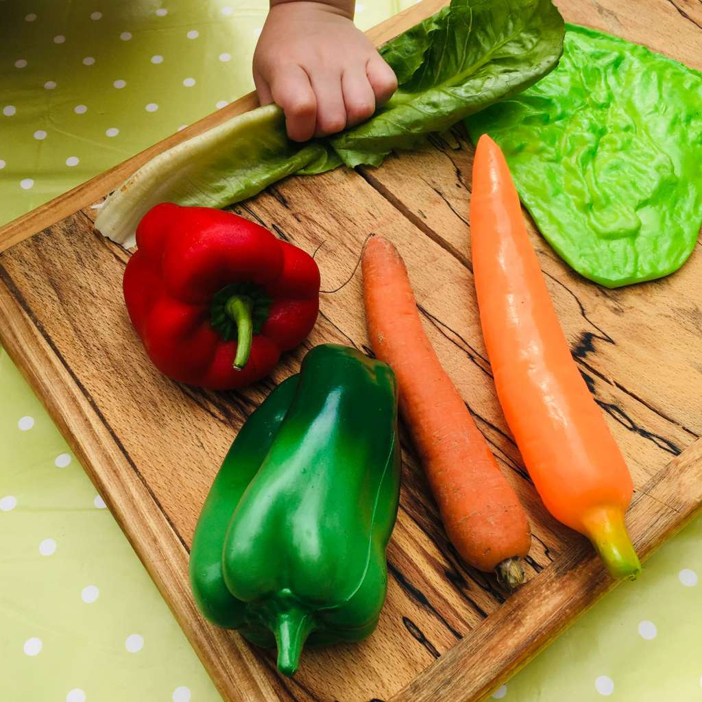 A wooden chopping board show display several vegetables - a pepper, a carrot and a lettuce lead - along with their plastic pretend-play counterparts