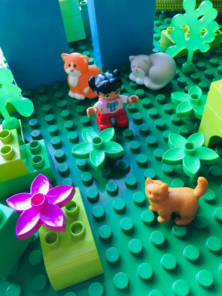A garden made of Duplo, with a small Duplo girl surrounding by toy cats