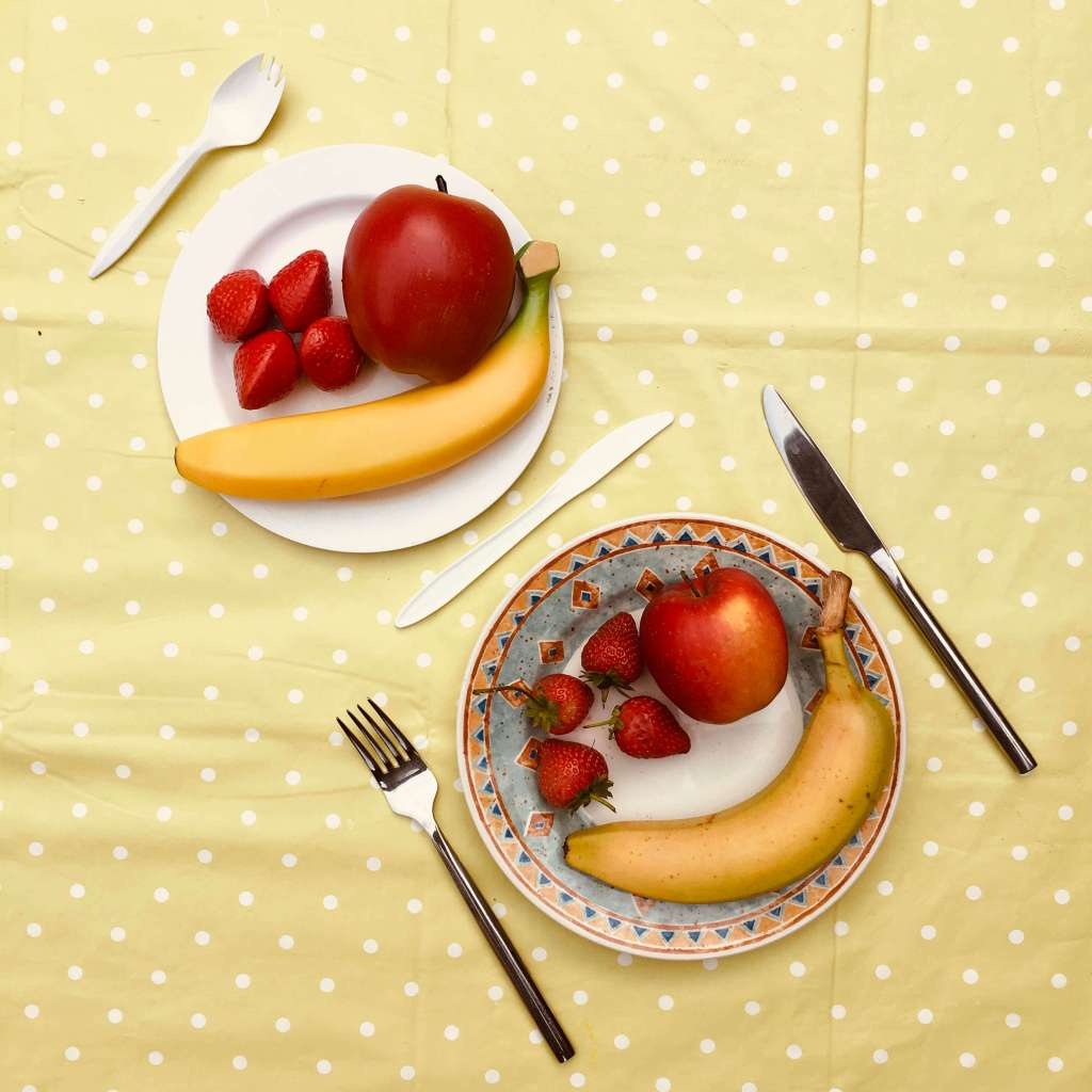 Two plates of food are contrasted, one is a china plate with apple, strawberries and banana, and metal cutlery. The other shows the same arrangement, except the food, crockery and cutlery are all plastic.