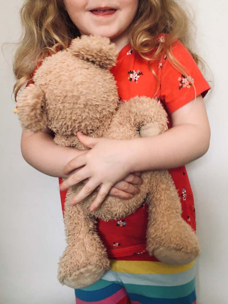A young girl smiles and hugs her teddy bear