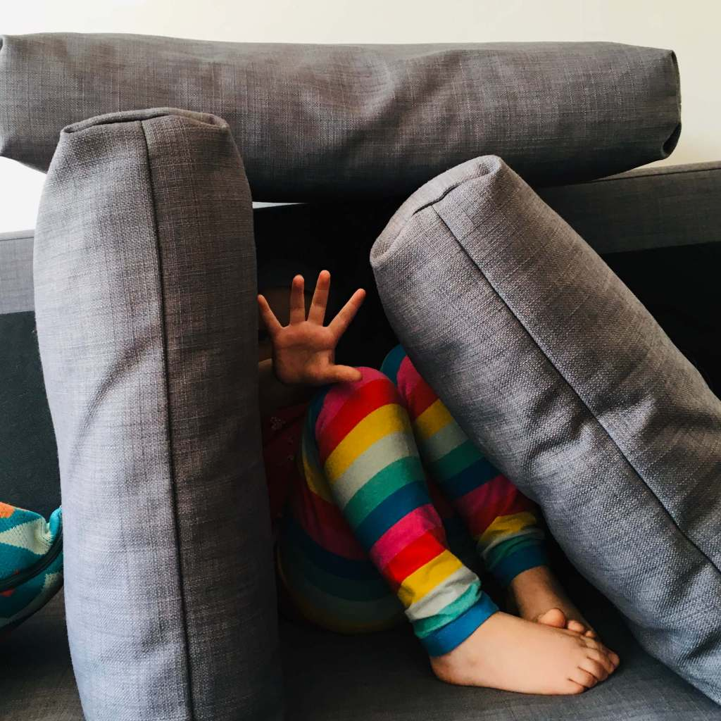 A child hides herself within a 'pillow fort' and holds her palm out to make it clear she wants to be left alone