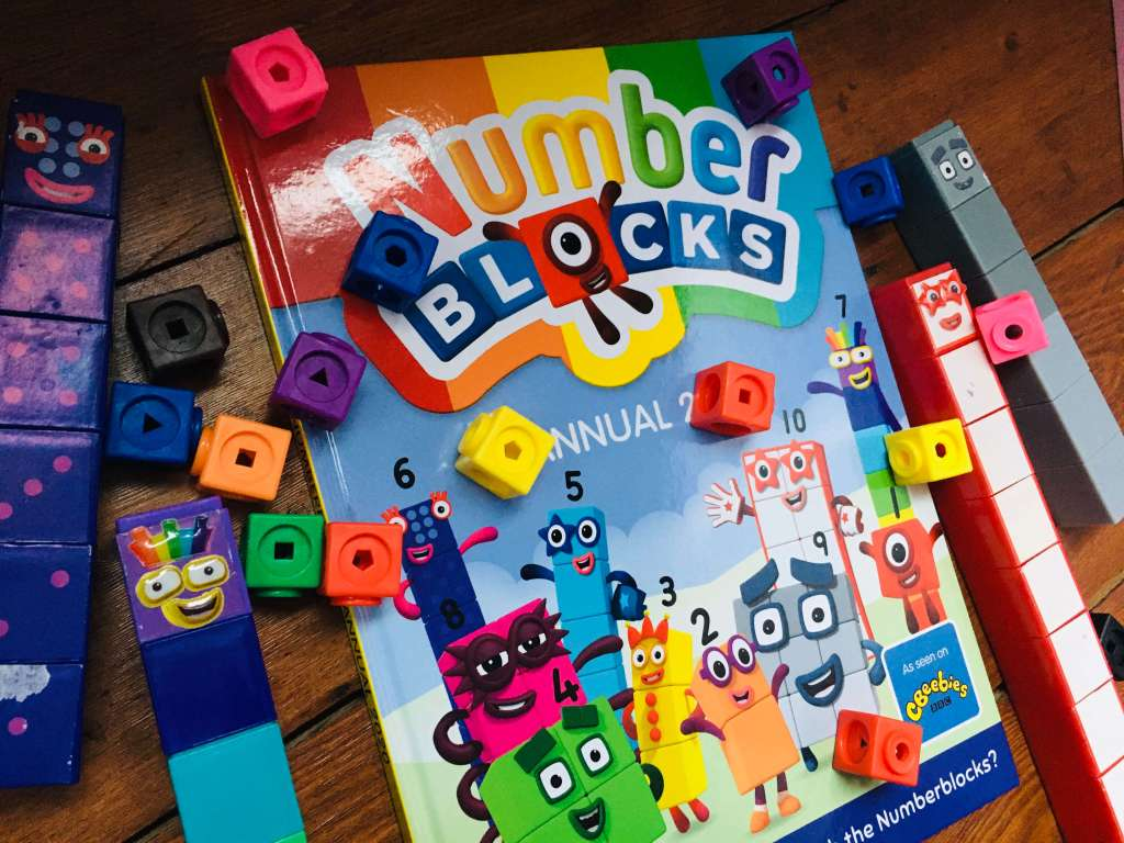 A Numberblocks 2020 annual is pictured, alongside some Numberblocks toys and multicoloured Mathlink Cubes