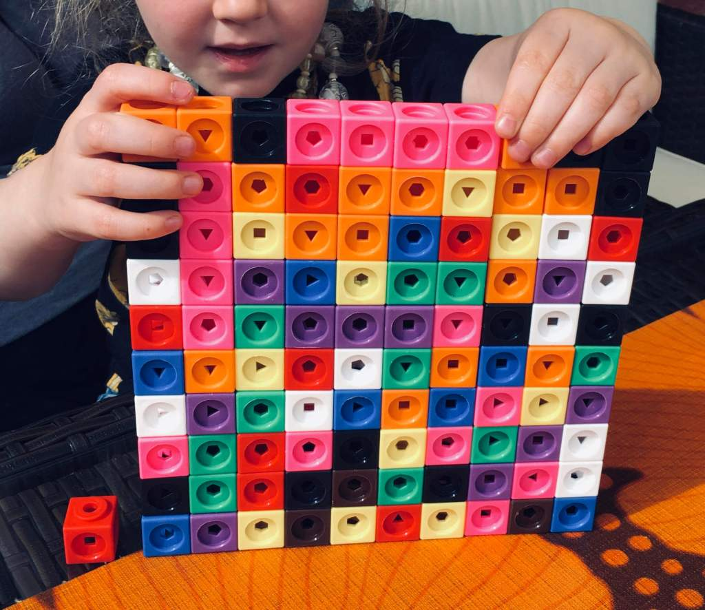 A young girl carefully positions the final cubes in a multicoloured square of Mathlink Cubes, to construct a 10 by 10 square made of 100 individual cubes. A single additional cube is left to one side, for scale.
