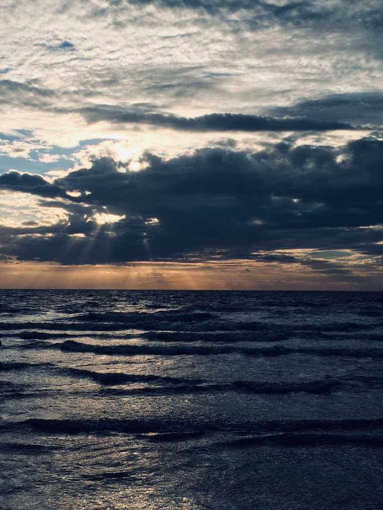 On the horizon, the glow of late evening sunlight is visible behind the clouds, shining onto dark and glittering waves as the tide comes in across a beach
