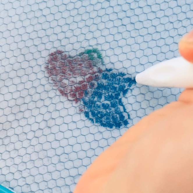 A child's overlays two heart-shaped stamps to create an image of a butterfly on a magnetic drawing board