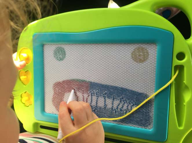 A child's draws a face on a magnetic drawing board, rendering the eyes and lips using a circular stamps and the teeth with her stylus