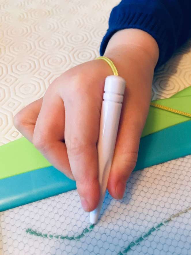 A child's using a three-finger pencil grip on a magnetic drawing board