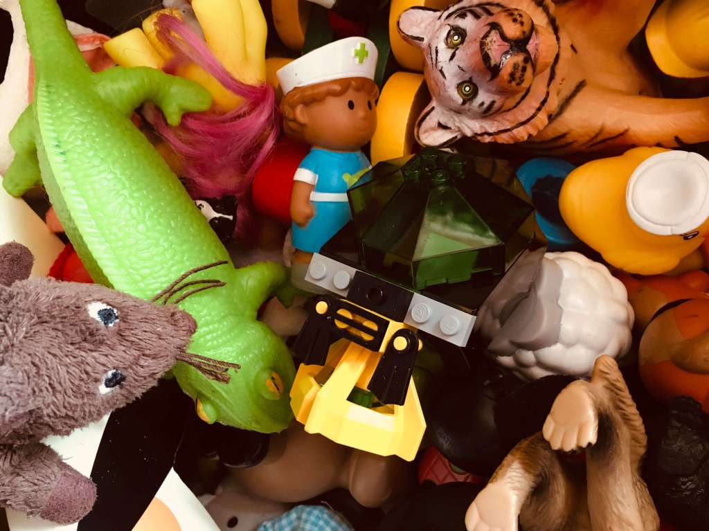 The cluttered contents of a toy box - lego, plastic animals, cuddly toys and dolls
