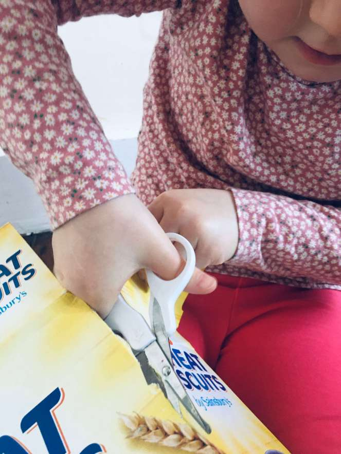 A girl uses a pair of scissors to cut up a cereal packet