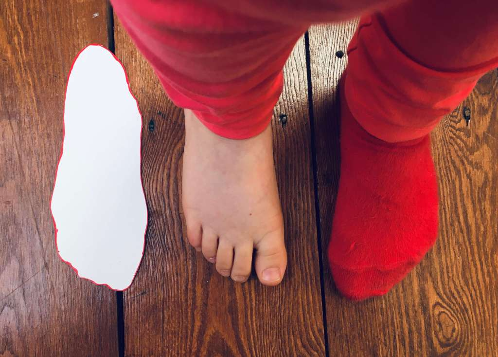 A child's feet are shown next to a cardboard template measure that was completed by drawing around her foot