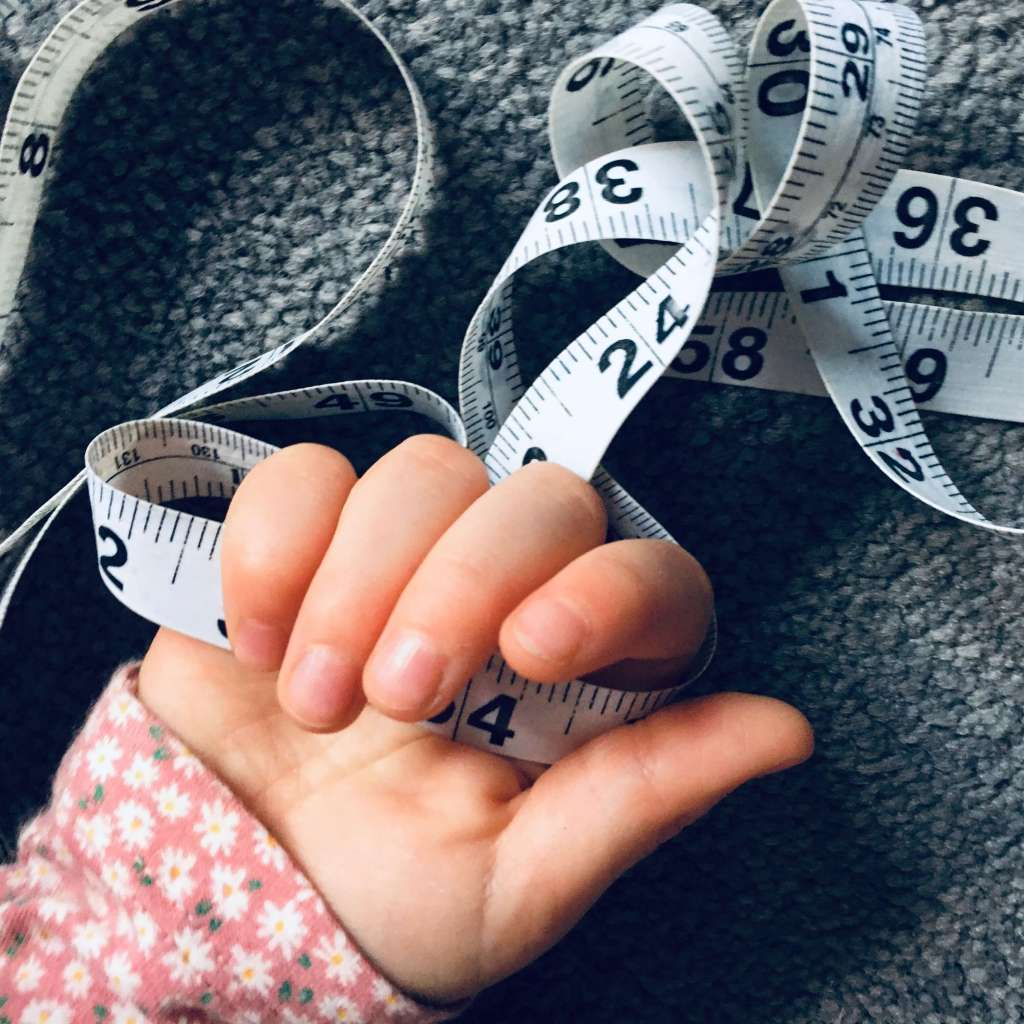 A child holds a coiled measuring tape in her hand