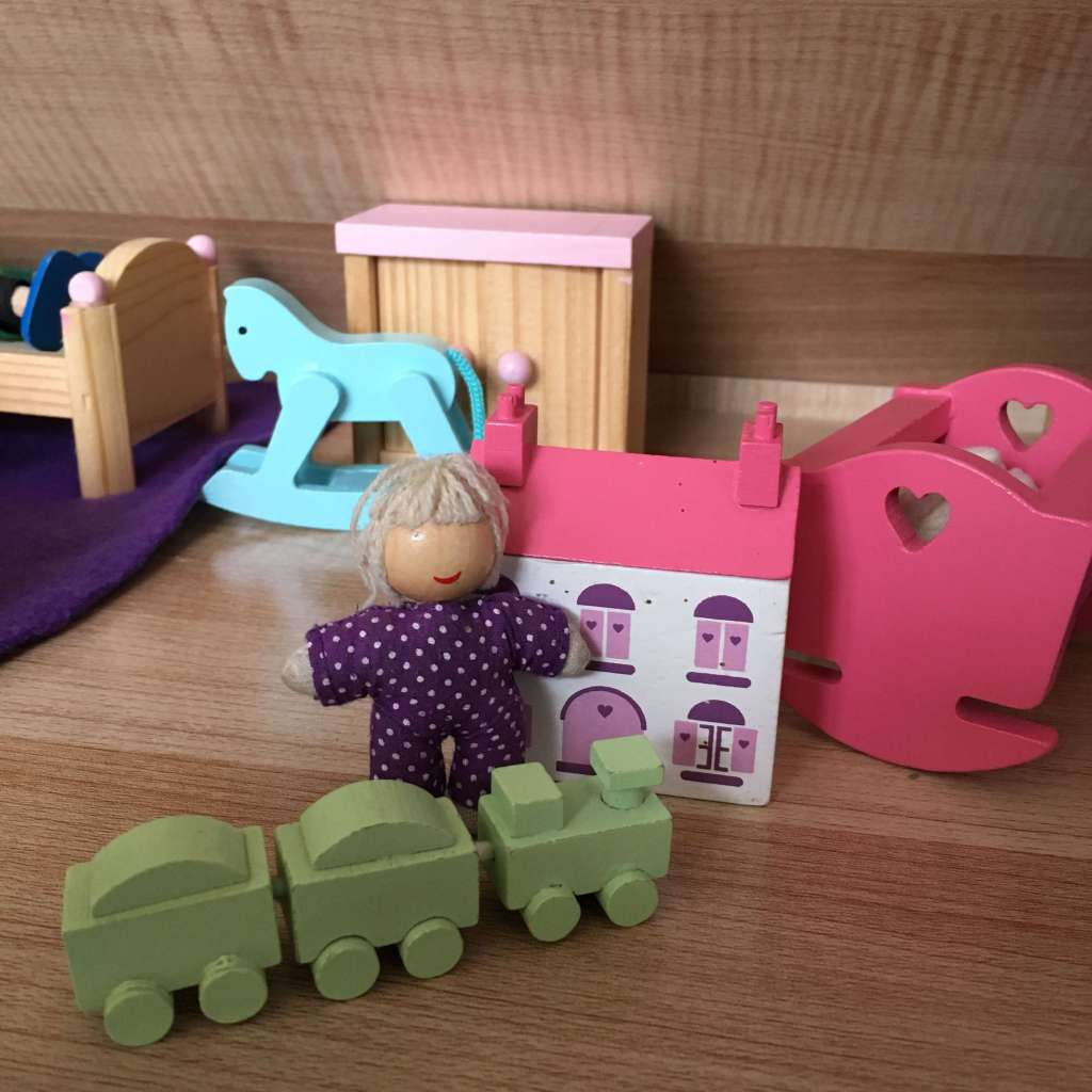 A wooden baby doll next to a tiny replica wooden doll's house, a tiny wooden train set and her little wooden crib, all within a large doll's house