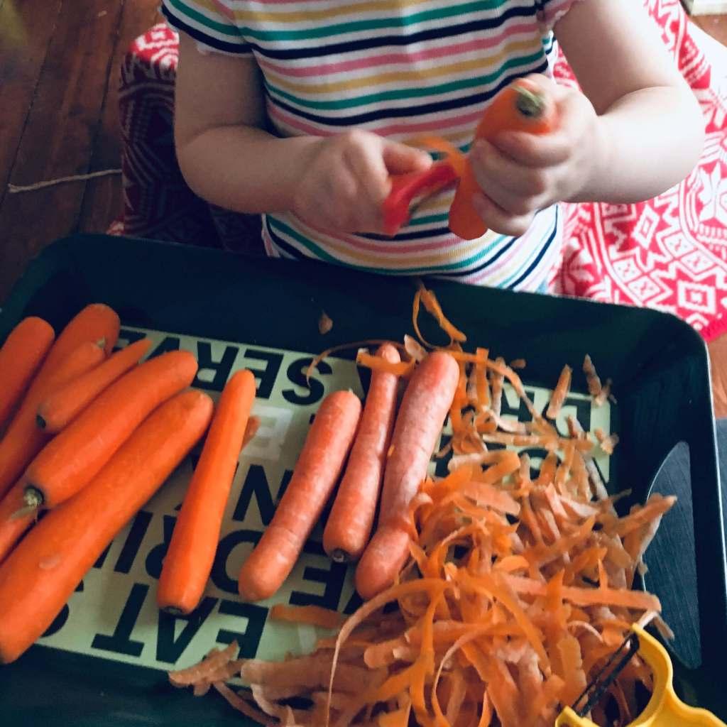 A girl peels carrots using a potato peeler