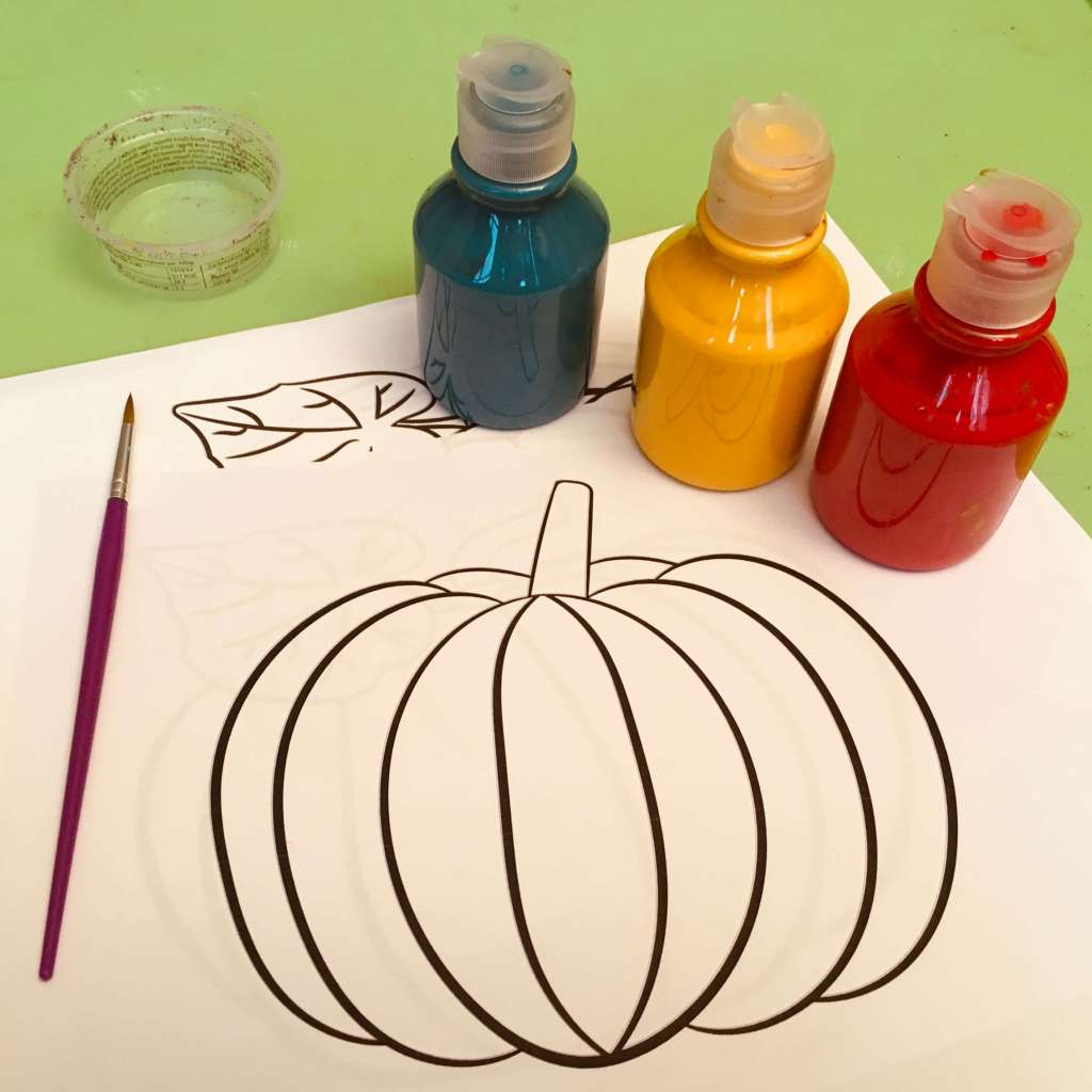 Three pots or primary colour poster paints, a paint brush and some printed paper images of pumpkins, ready to be painted