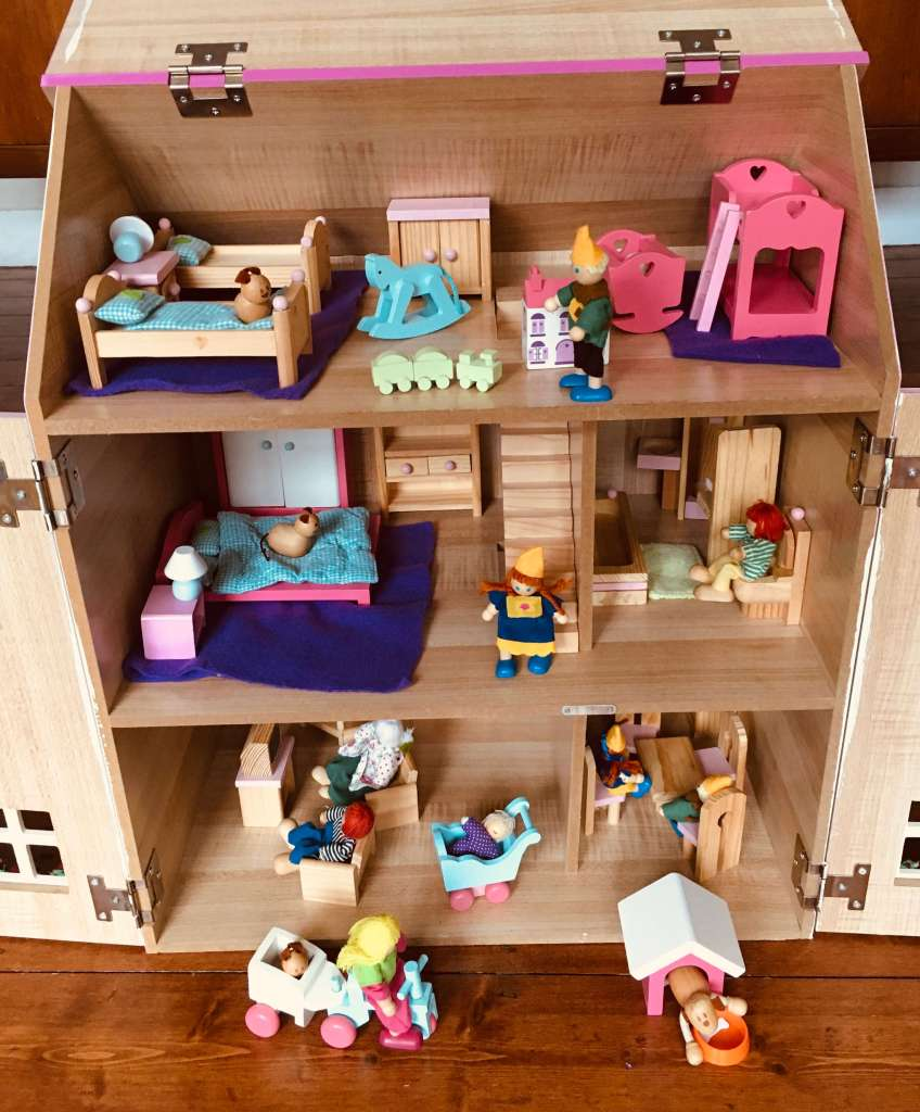 A child's wooden doll's house, populated with dolls and animals
