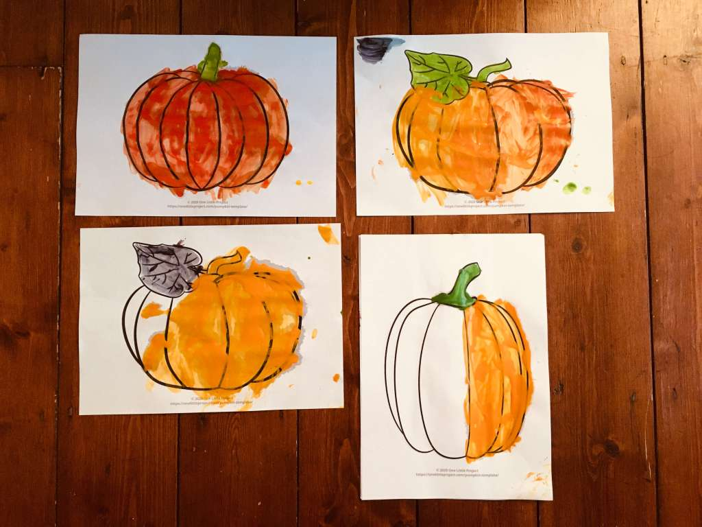 Four printed outlines of pumpkins on white paper, which have been painted by a child with various shades of paint